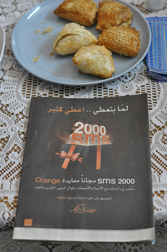 Plate of borekas and Arabic language cellphone ad for Orange.